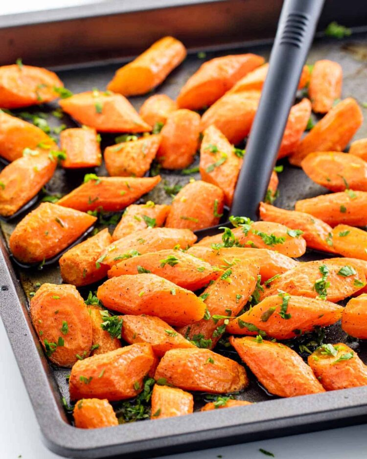 a spatula holding some roasted carrots in a baking pan