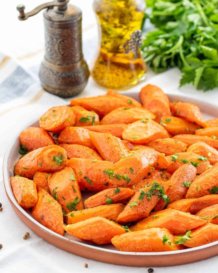 roasted carrots in a white plate garnished with parsley
