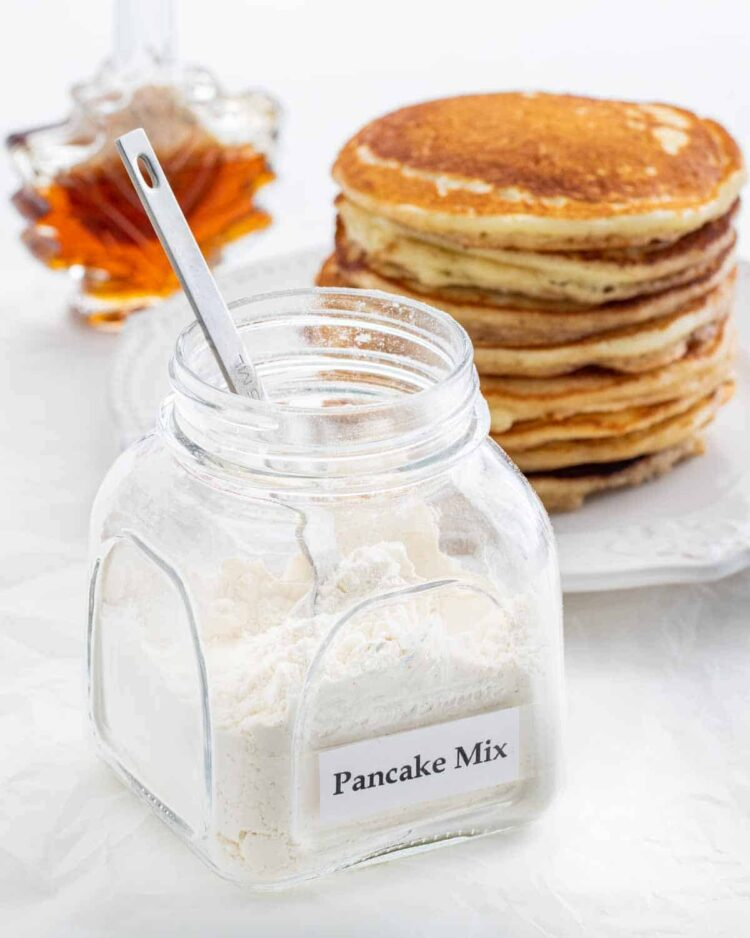 a jar with pancake mix and a stack of pancakes in the background