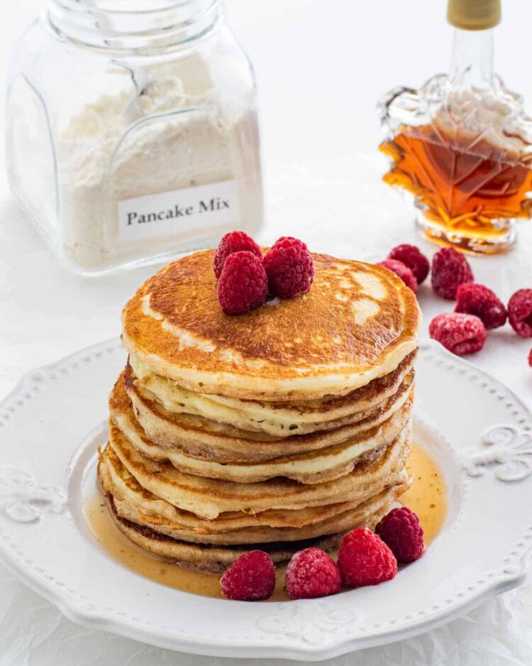 a stack of pancakes on a white plate garnished with raspberries