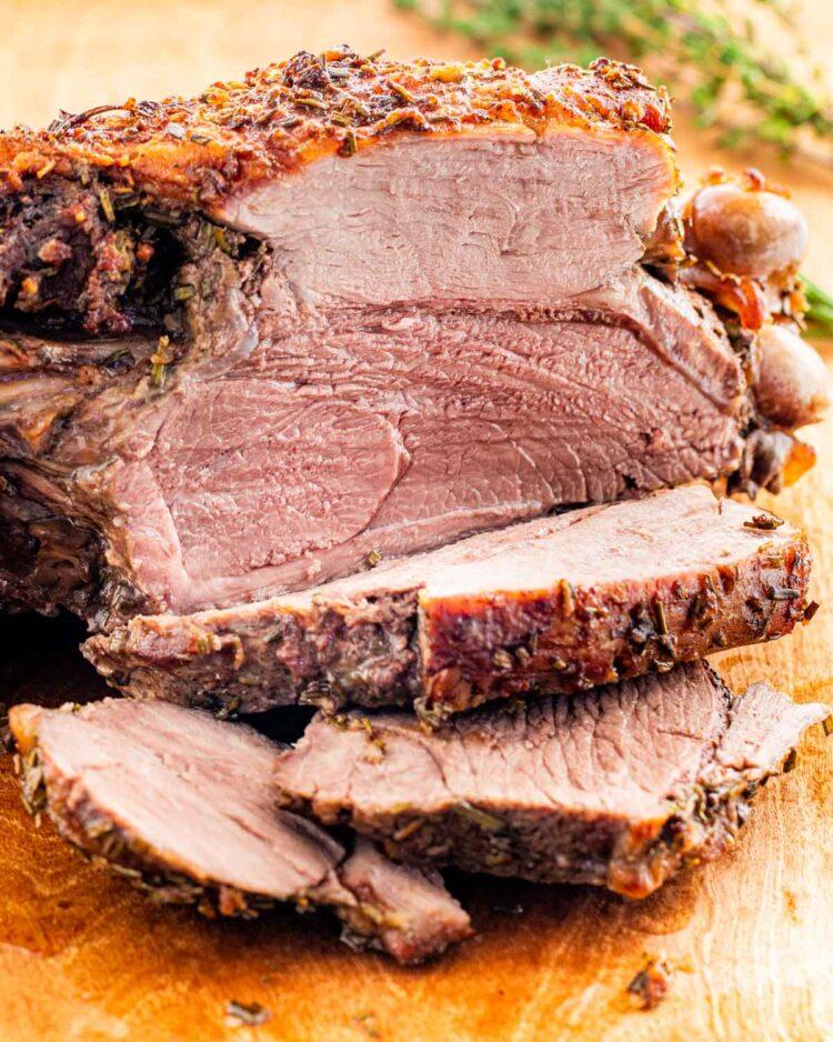 a sliced roast leg of lamb on a cutting board