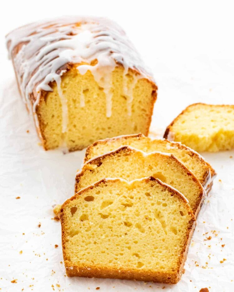 a delicious homemade lemon loaf cut into slices with a lemon glaze on parchment paper