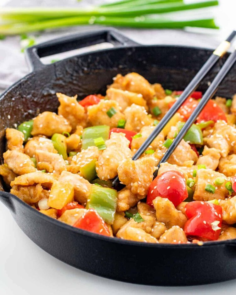 sweet and sour chicken in a black skillet with chopsticks