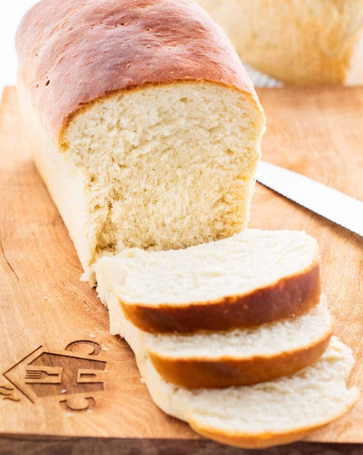 a amish white bread on a cutting board with 3 slices of bread