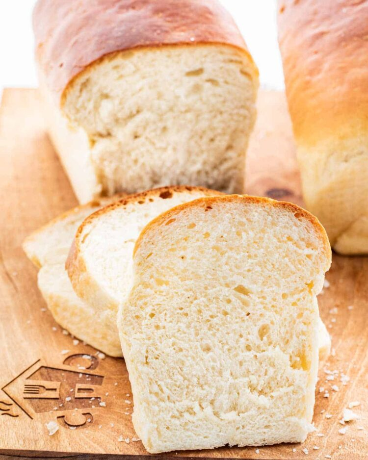 closeup shot of a few slices of bread on a cutting board with the rest of the loaves in the background