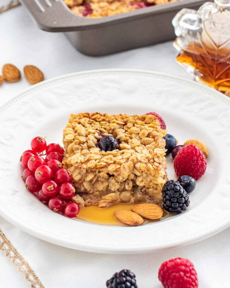 a slice of baked oatmeal garnished with berries and maple syrup on a white plate