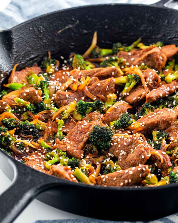 beef and broccoli in a black skillet garnished with sesame seeds