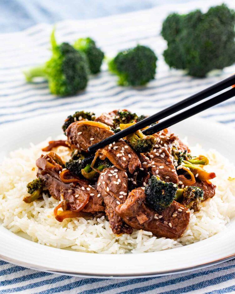 beef and broccoli over a bed of rice garnished with sesame seeds and a pair of chopsticks picking up a piece of meat