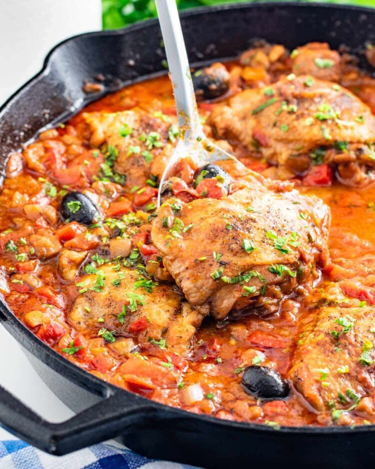 side shot of freshly made chicken cacciatore in a black skillet with a serving spoon inside lifting a chicken thigh