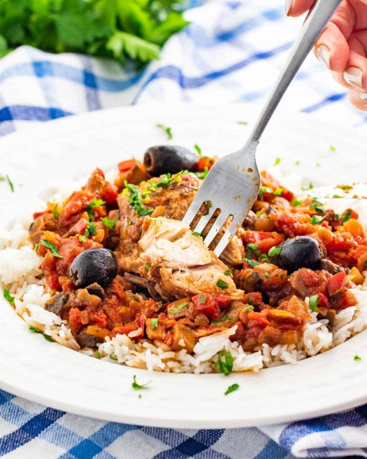 side shot of chicken cacciatore over a bed of rice with a fork holding a piece of chicken