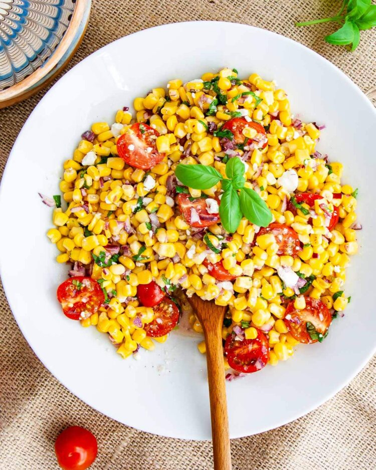 overhead shot of corn salad in a white plate with a wooden spoon inside and a basil leaf on top