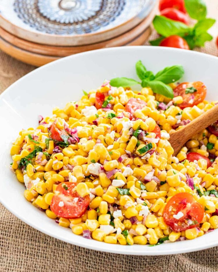 side shot of delicious and vibrant corn salad in a white bowl with a wooden spoon inside