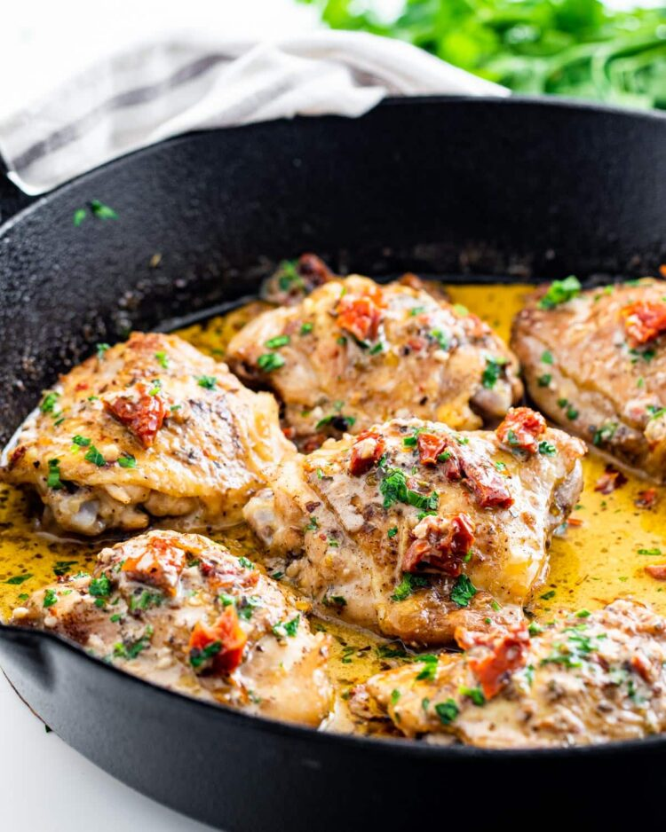 side shot of chicken thighs in a black skillet with a creamy sun-dried tomato sauce