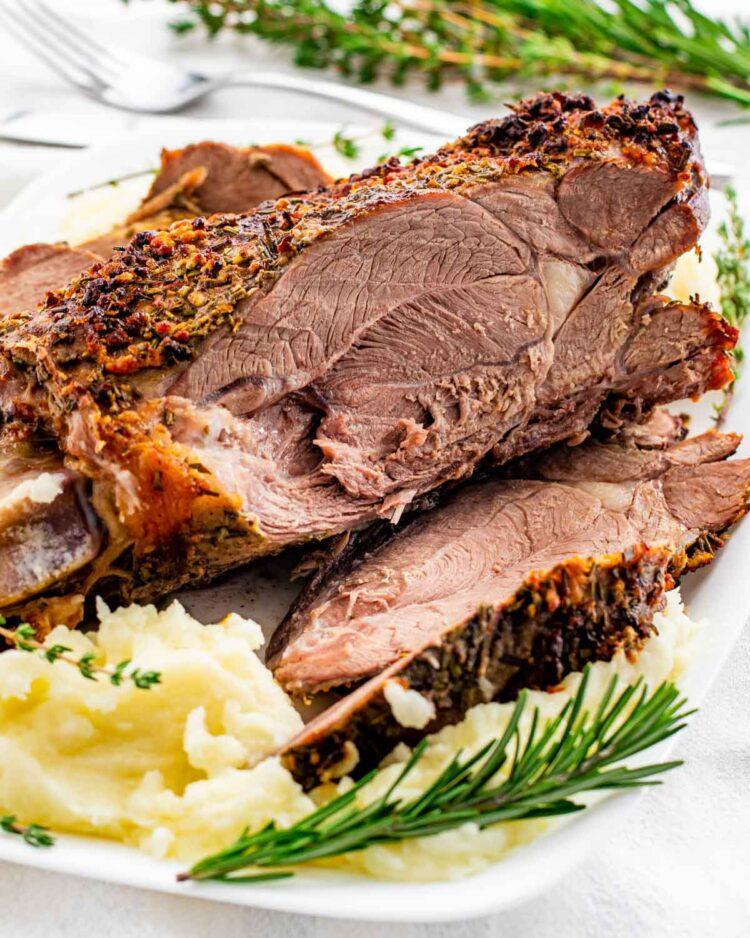 sliced up roast leg of lamb over mashed potatoes garnished with rosemary