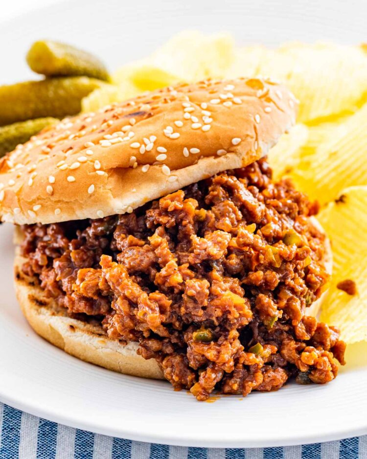 a sloppy joe sandwich with chips on a plate