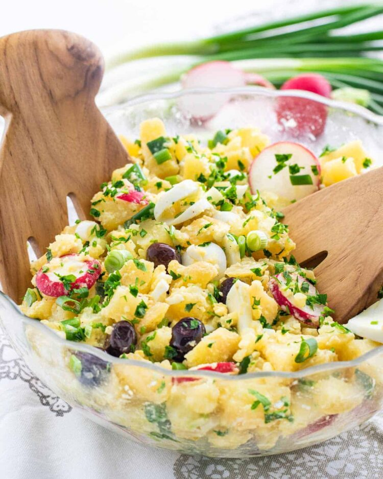 a glass bowl full of spring potato salad with two tossing salad hands in it