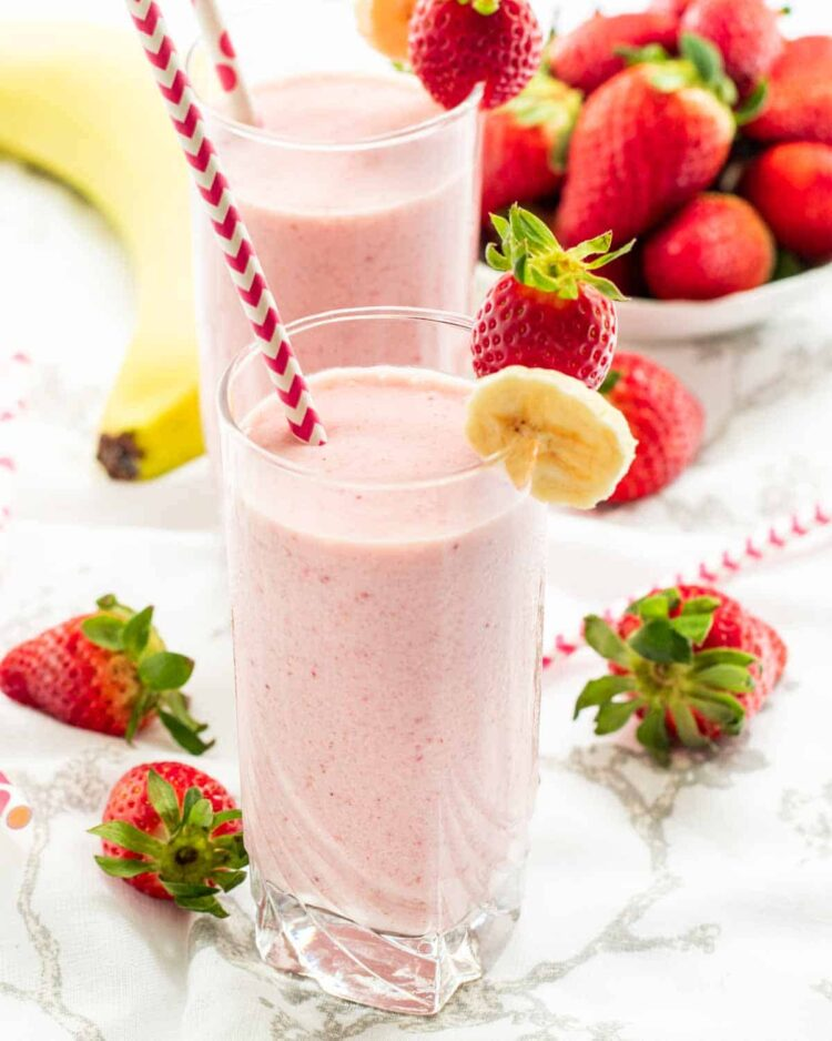 two glasses filled with strawberry banana smoothie  surrounded by strawberries