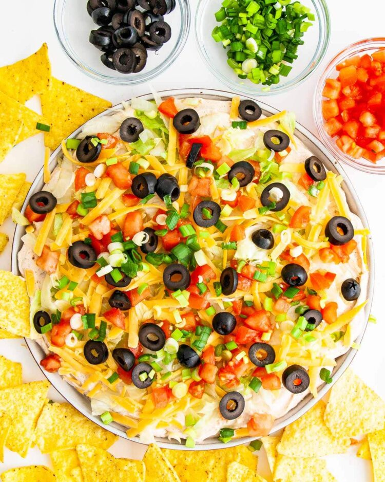 overhead shot of taco dip on a platter topped with cheese, olives, tomatoes and green onions