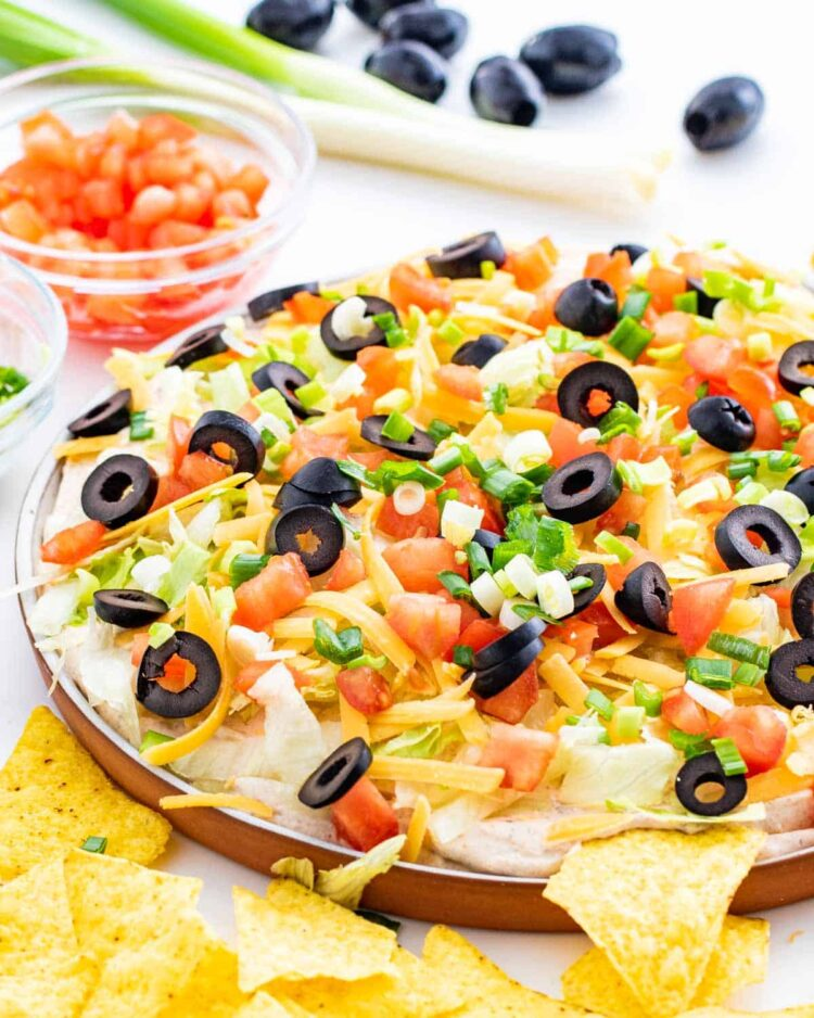 taco dip on a platter topped with cheese, olives, tomatoes and green onions
