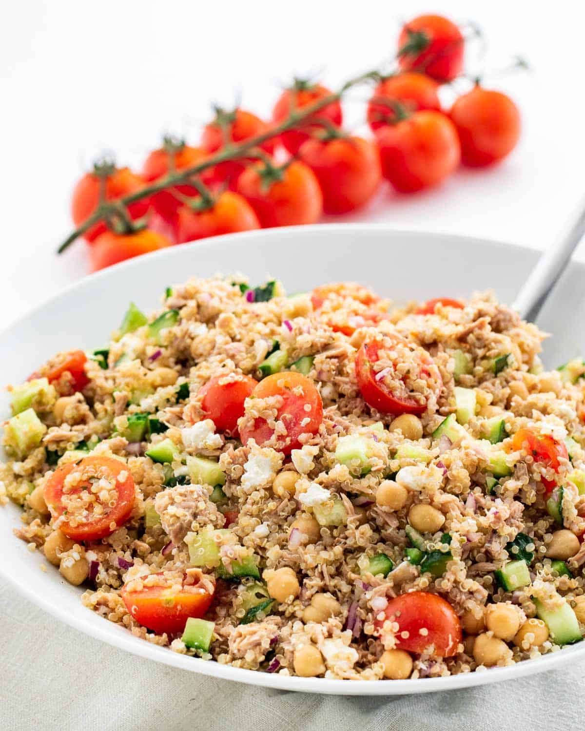 tuna quinoa salad with tomatoes and cucumbers in a white bowl