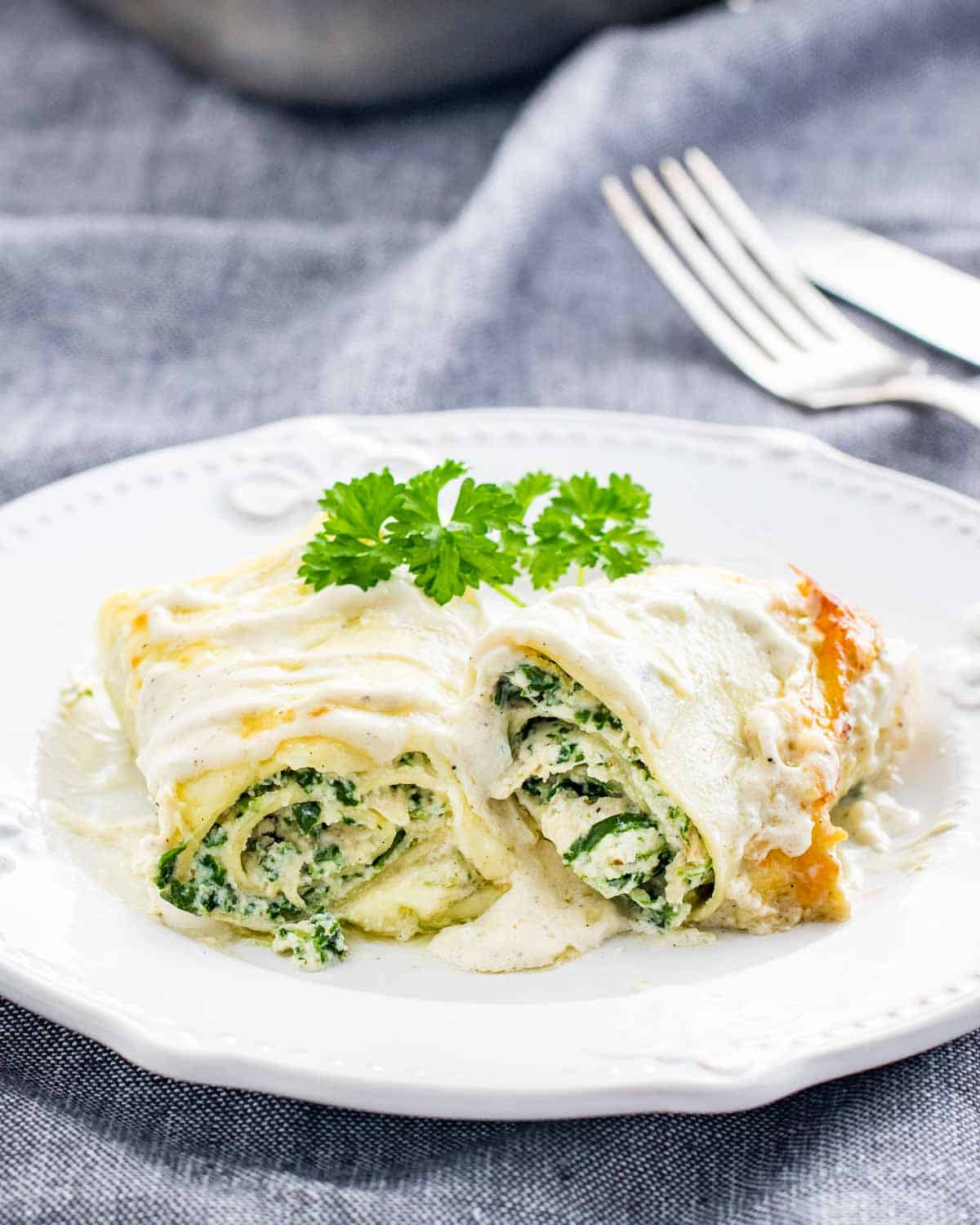 a lasagna roll up cut in half on a white plate garnished with parsley