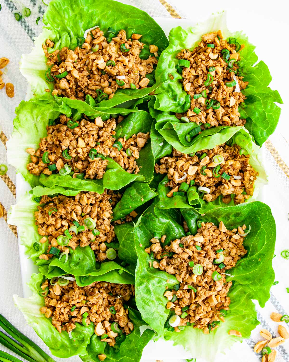 overhead shot of a bunch of asian lettuce wraps on a white platter garnished with peanuts