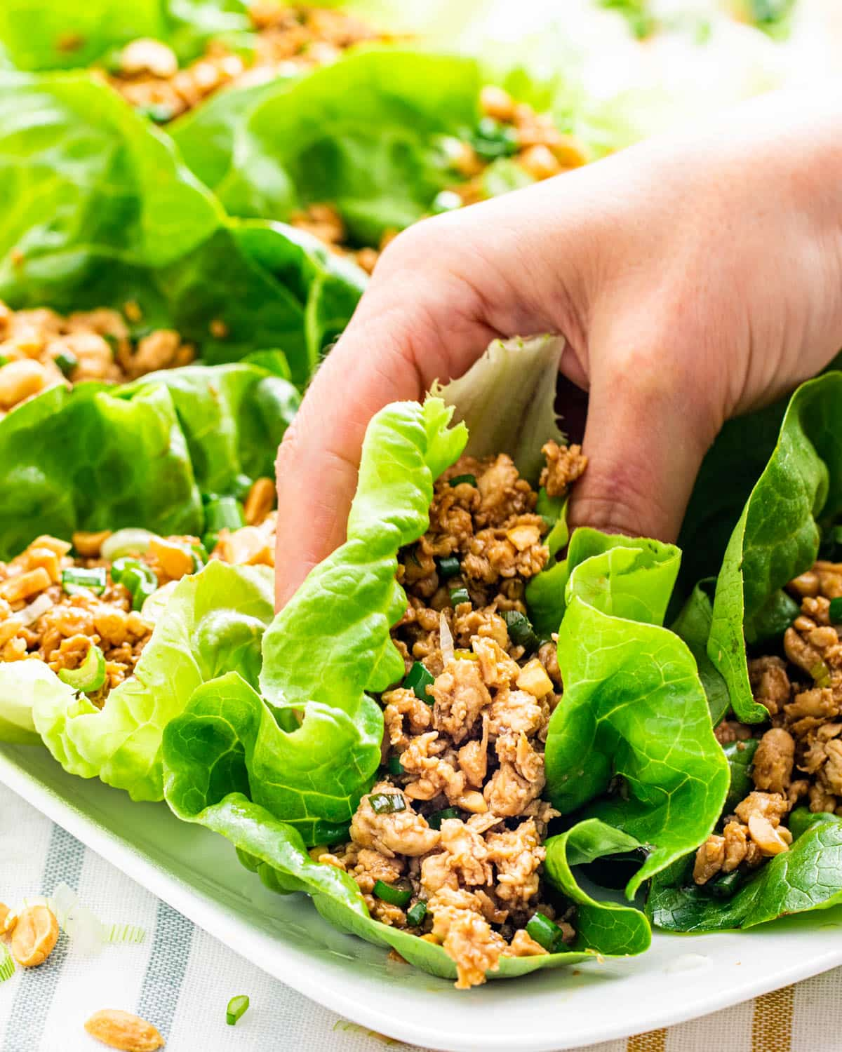 a hand holding a lettuce wrap  over a platter with other lettuce wraps