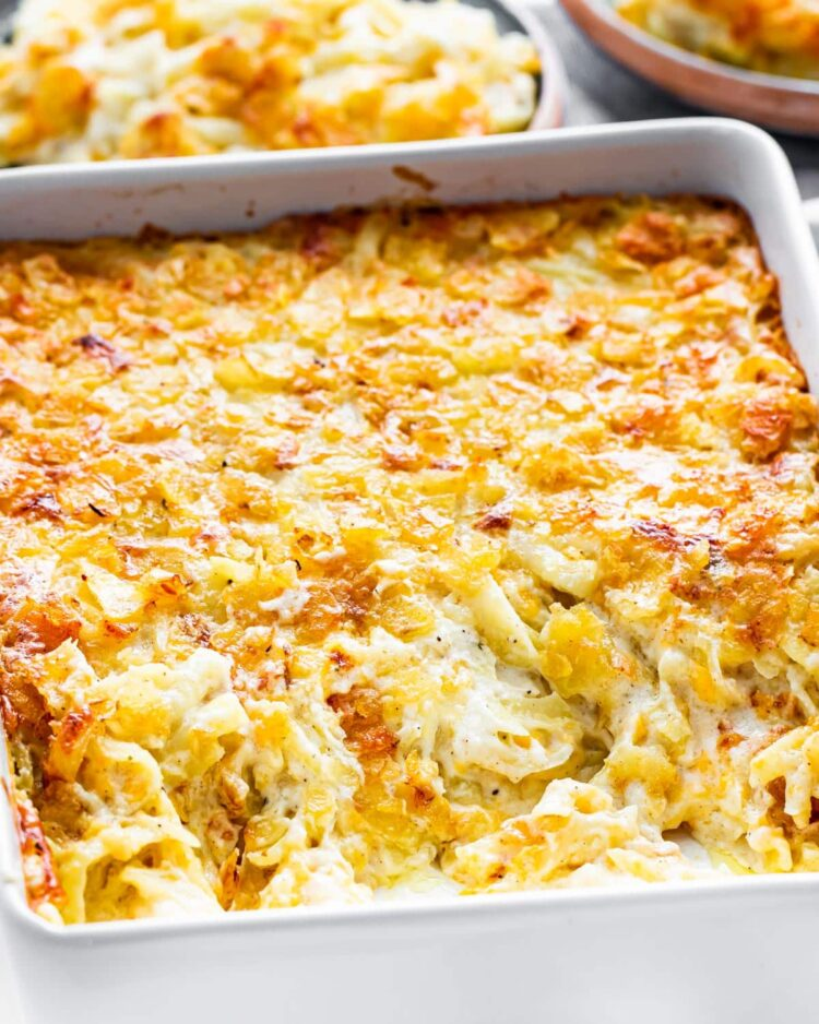 side view shot of cheesy potato casserole in a casserole dish with some already scooped out