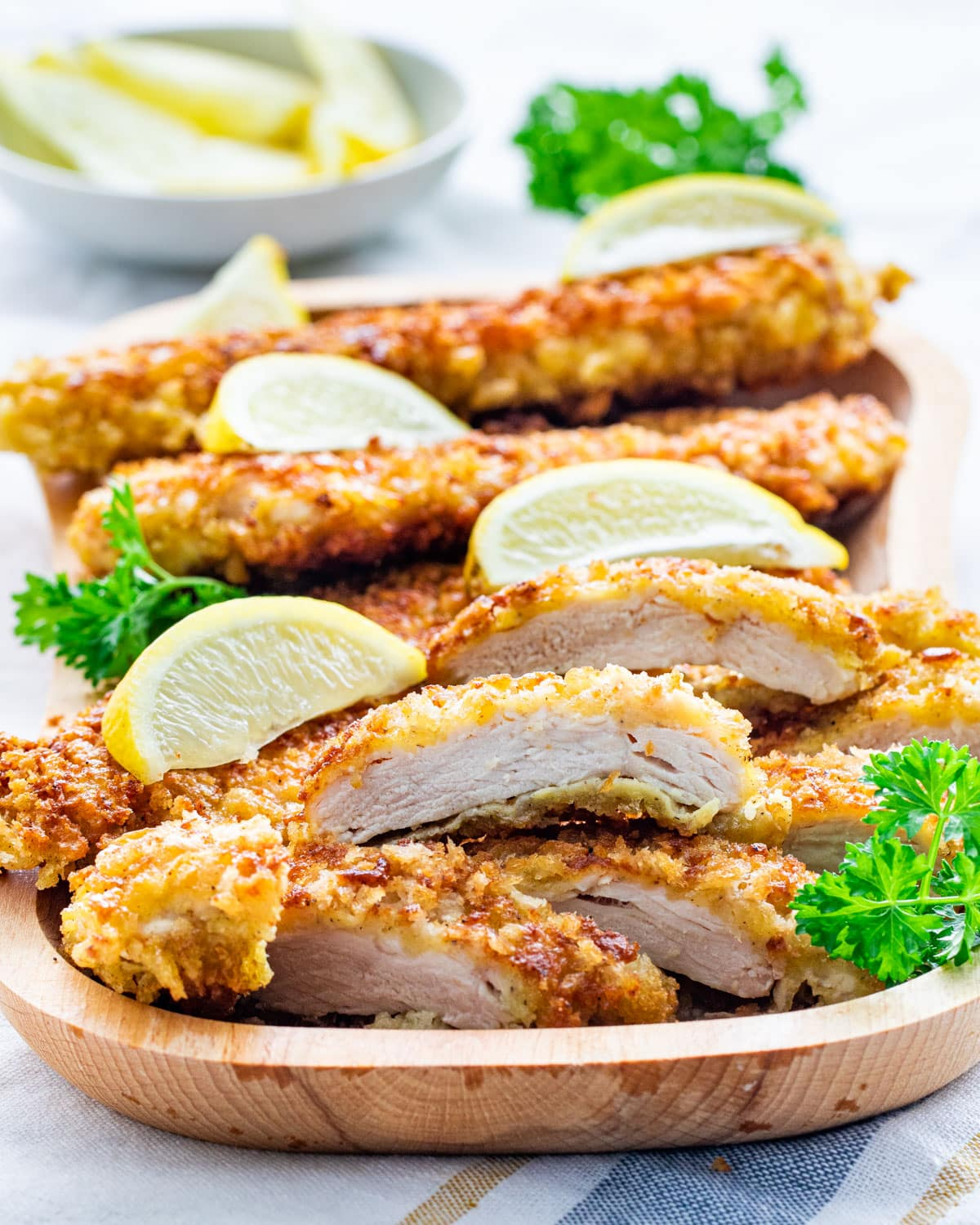 crispy chicken cutlets cut into pieces on a wooden plate garnished with lemon wedges and parsley