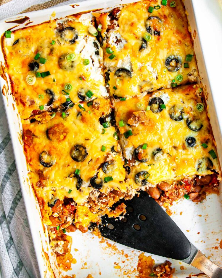 overhead shot of mexican casserole in a casserole dish cut into slice and 2 slices missing