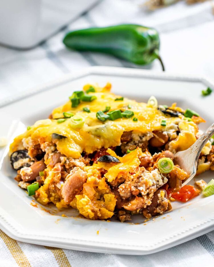 a slice of mexican casserole on a white plate with a fork inside