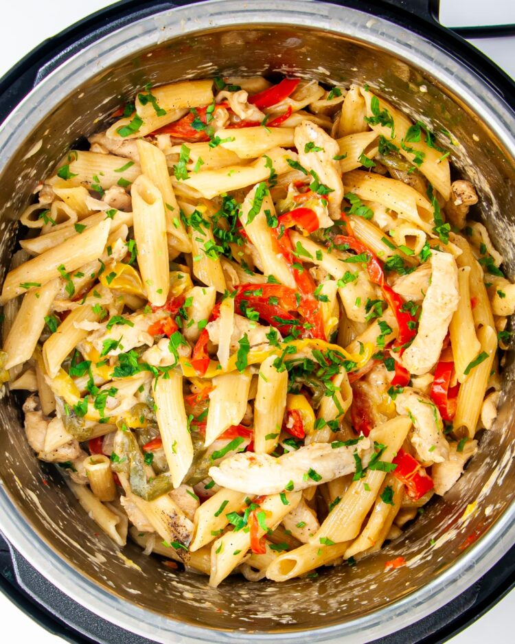overhead shot of freshly made chicken fajita pasta in an instant pot garnished with a bit of cilantro