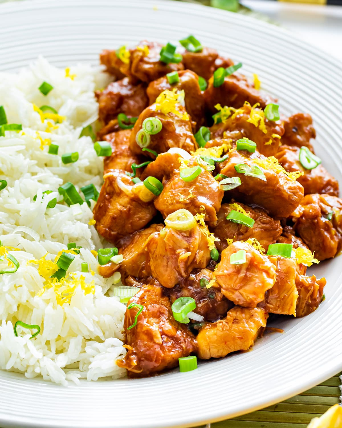 orange chicken on a white plate next to a bed of rice garnished with green onions and lemon zest