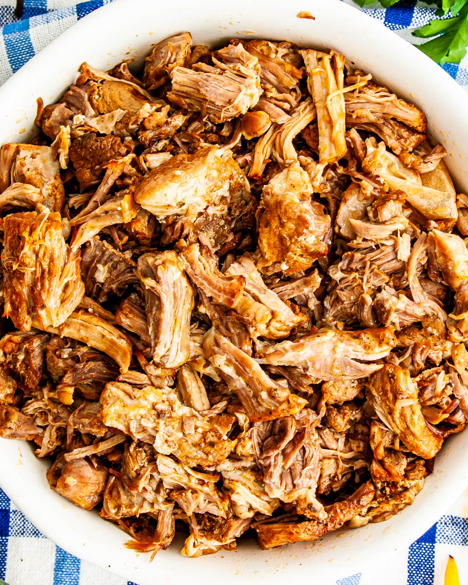 overhead shot of freshly made pork carnitas in a white bowl