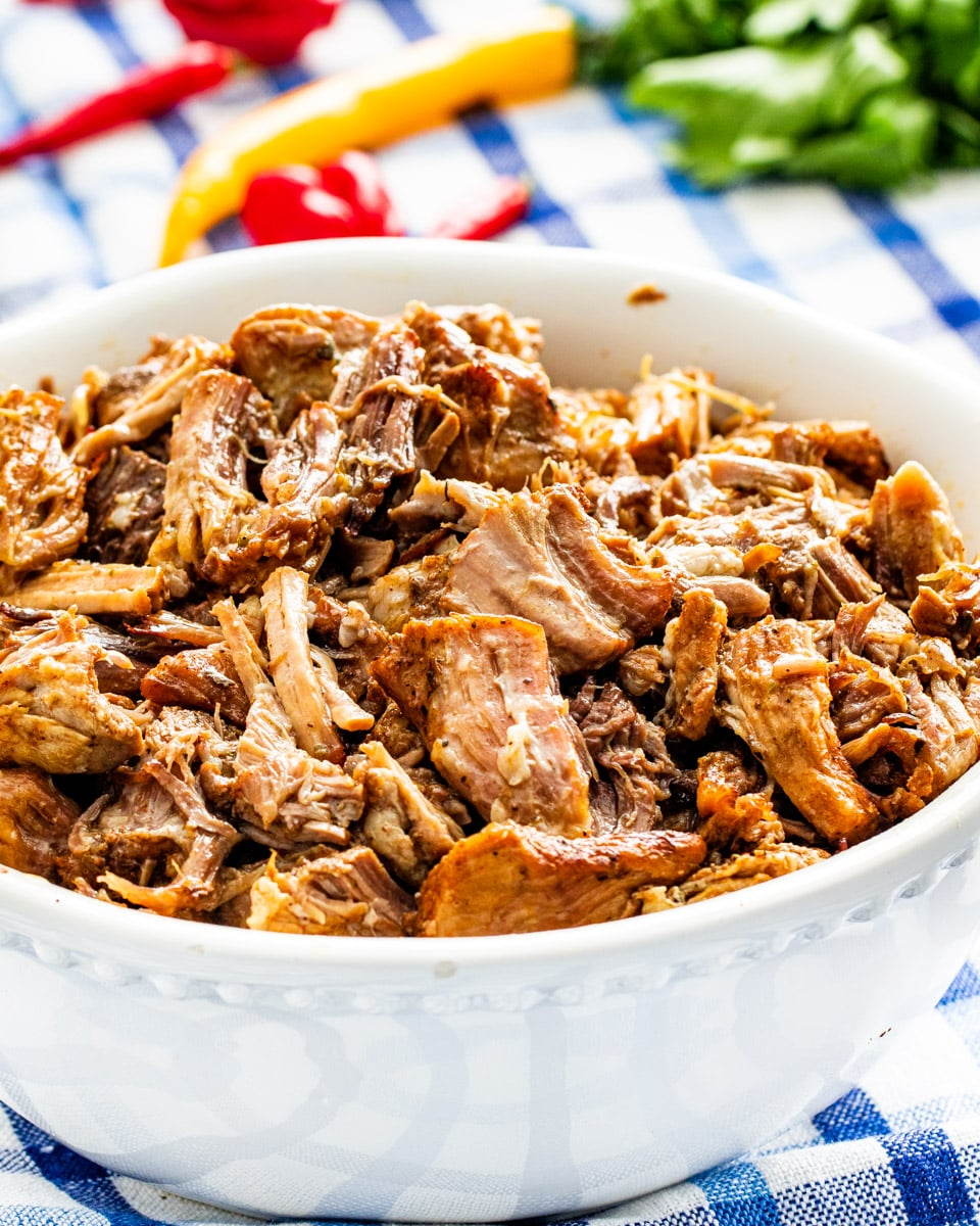 side shot of shredded pork carnitas in a white bowl
