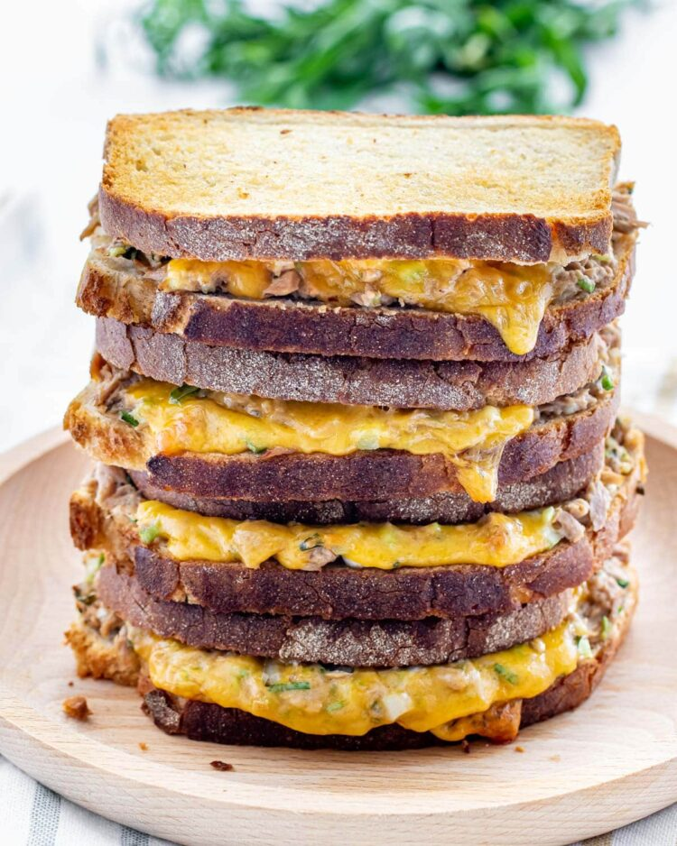 a gorgeous stack of tuna melts on a wooden plate