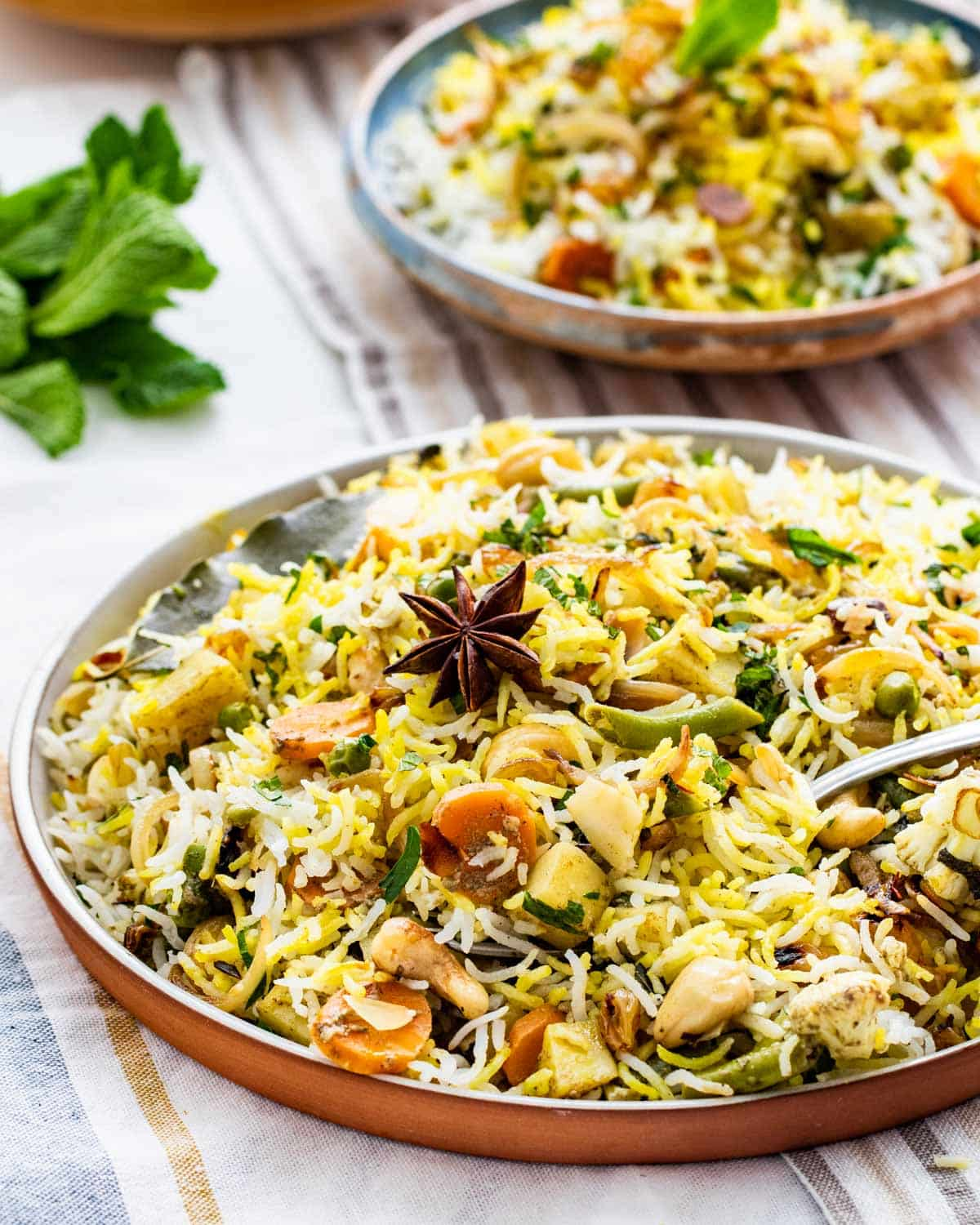 side view shot of a gorgeous plate full of vegetable biryani with a fork in it