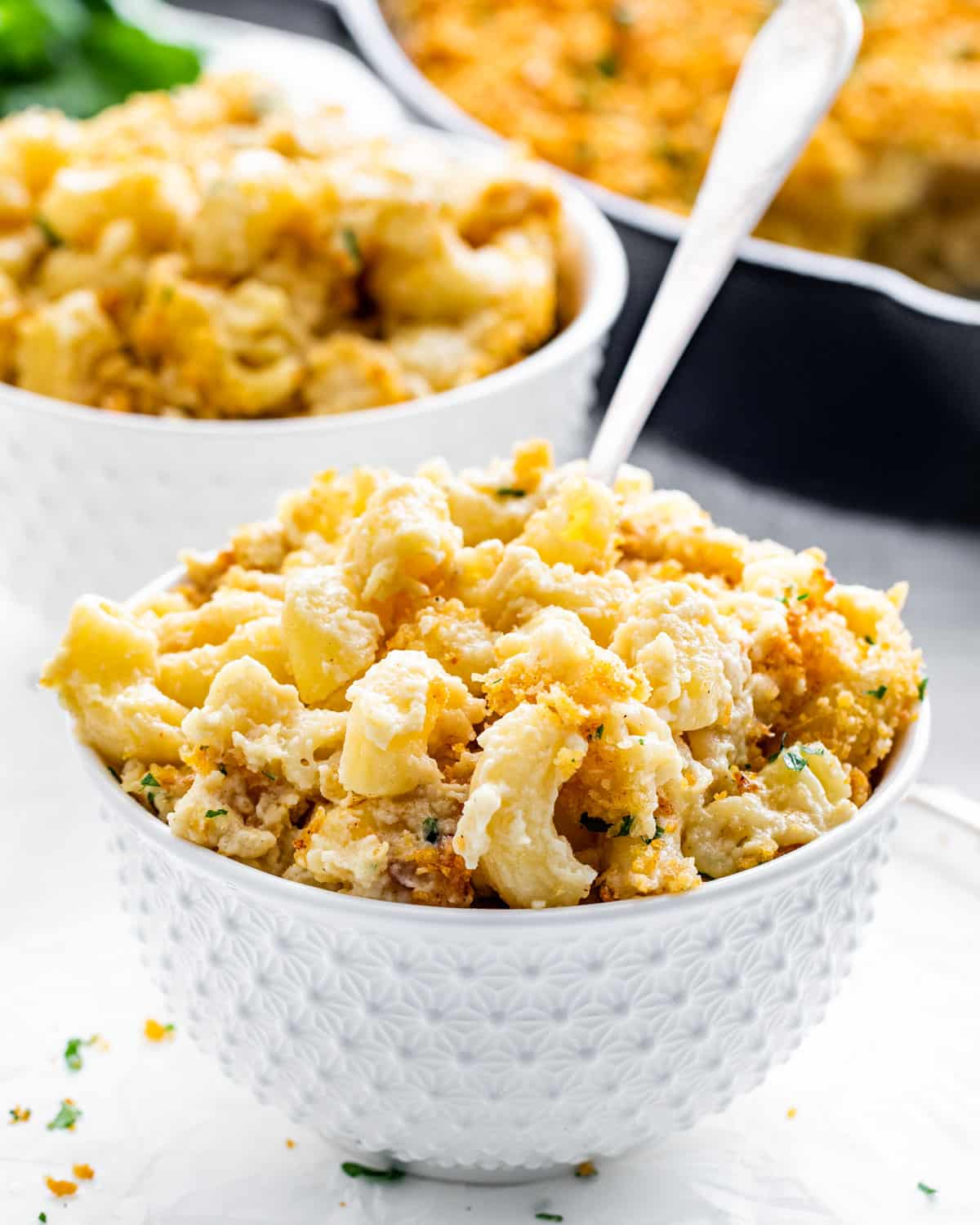a white bowl filled with baked mac and cheese with a fork inside