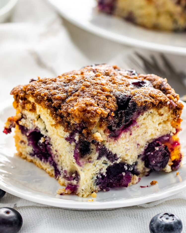 a gorgeous slice of blueberry buckle on a white dessert plate