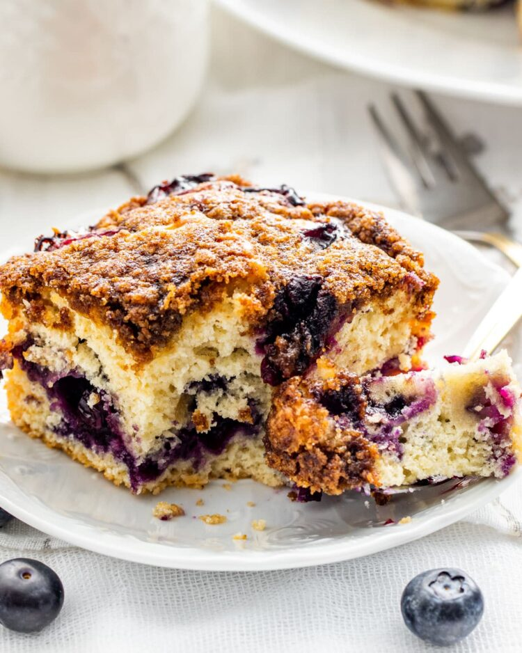 a slice of blueberry buckle on a white dessert plate with a bite take out of it