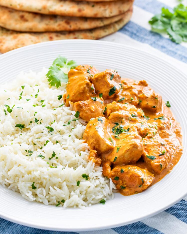 butter chicken in a white plate next to a side of rice