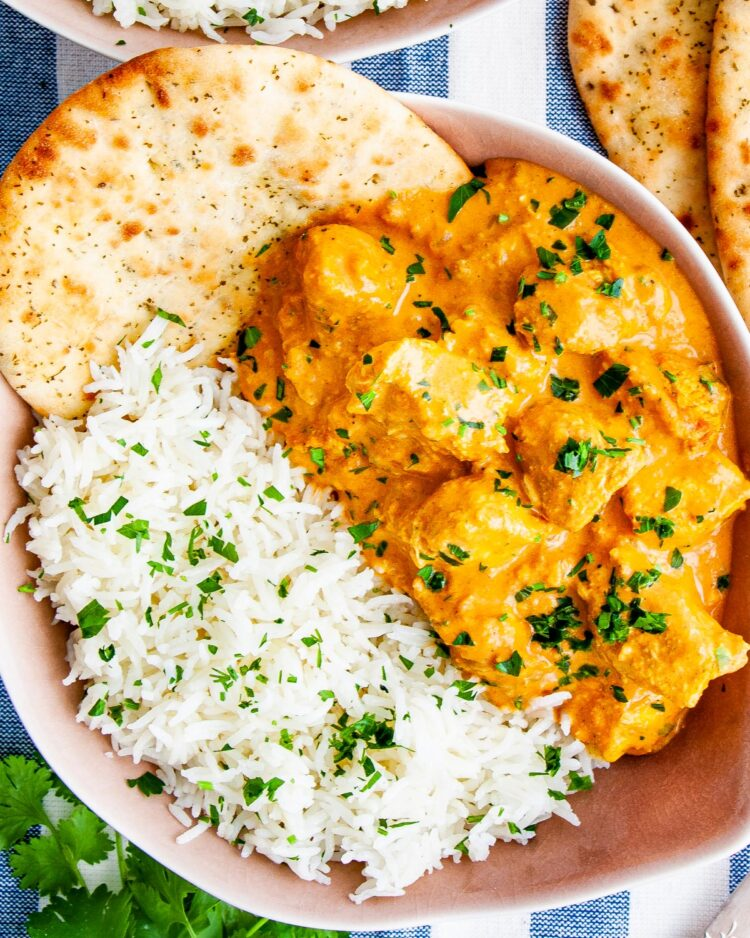 overhead shot of butter chicken in a pink plate next to a side of rice garnished with parsley and a slice of naan