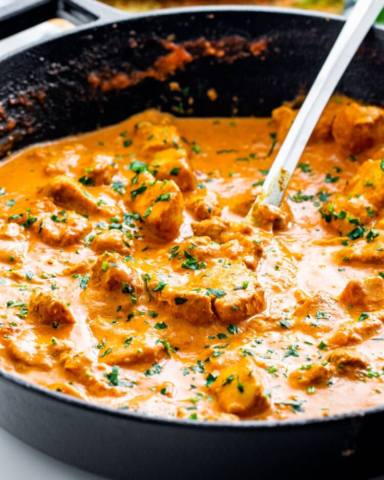 side view shot of freshly made butter chicken garnished with parsley in a black skillet