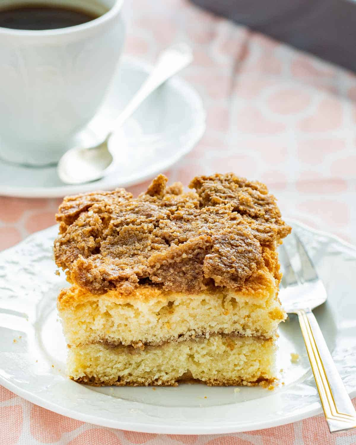 a full slice of freshly made coffee cake on a white plate with a cup of coffee in the background