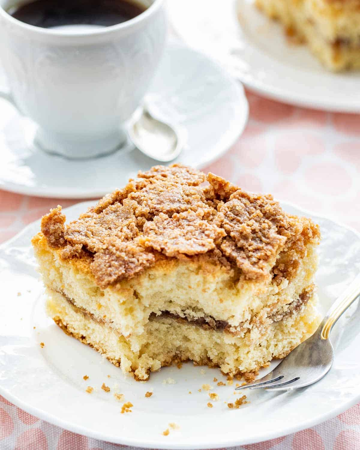 a slice of coffee cake on a white plate with a bite taken out of it and a cup of coffee in the background