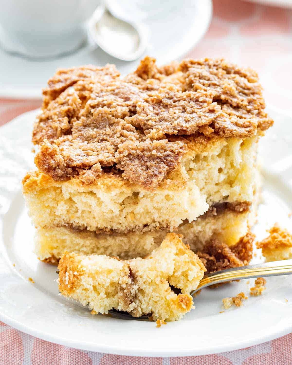 a full slice of coffee cake on a white plate with a fork and a bite taken out of it