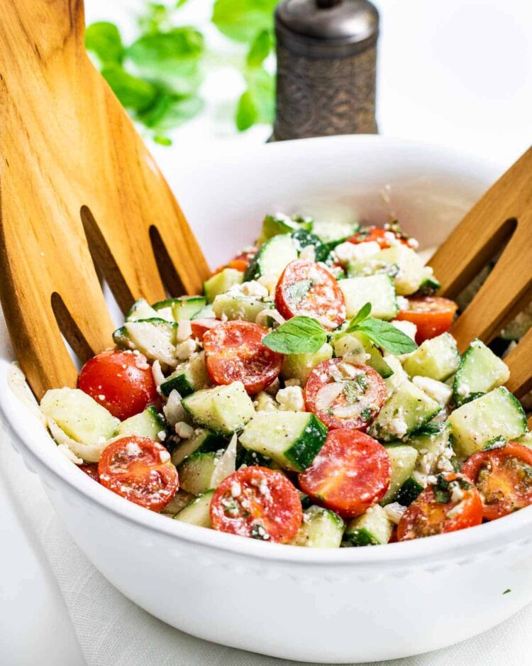 side view shot of cucumber tomato salad in a white bowl with two salad hands in it