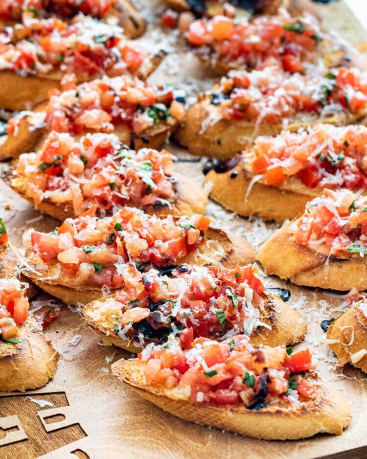 a couple rows of bruschetta on toasted baguette topped with parmesan cheese