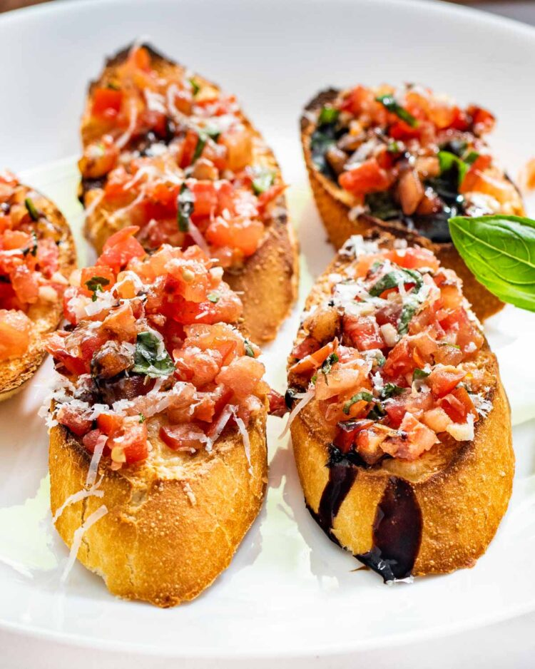 sideview shot of a few bruschetta slices on a white plate