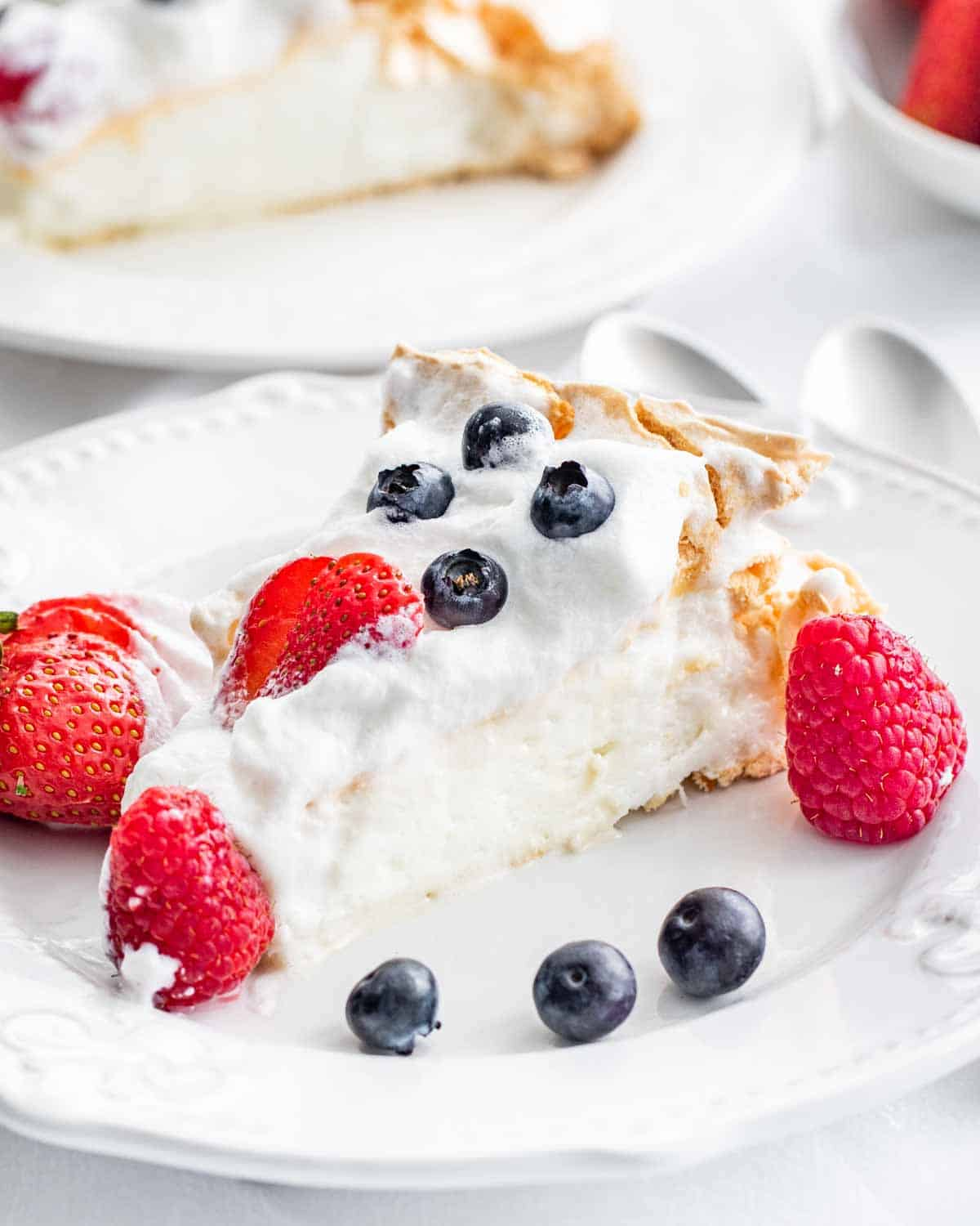 a gorgeous slice of a pavlova topped with whipped cream and berries
